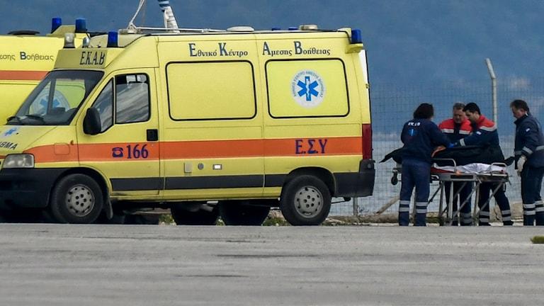 Räddningsarbetare tar hand om en kropp efter att minst tolv människor drunknat utanför Greklands västra kust.