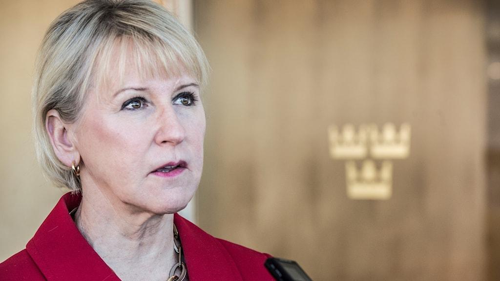 Kvinna framför vägg med riksdagens emblem med tre kronor.