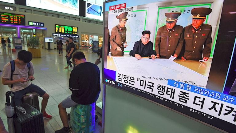 Två personer sitter och tittar på sina telefoner bredvid en tv-skärm som visar Kim Jong-Un.