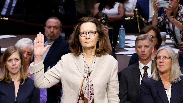 Kvinna med handen höjd.