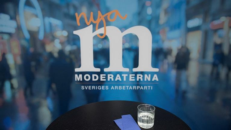 Ett tomt bord syns framför Moderaternas logotyp.