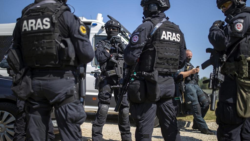 Den litauiska polisens anti-terroroperationsenhet ARAS anländer till ett av flyktinglägren i Litauen.