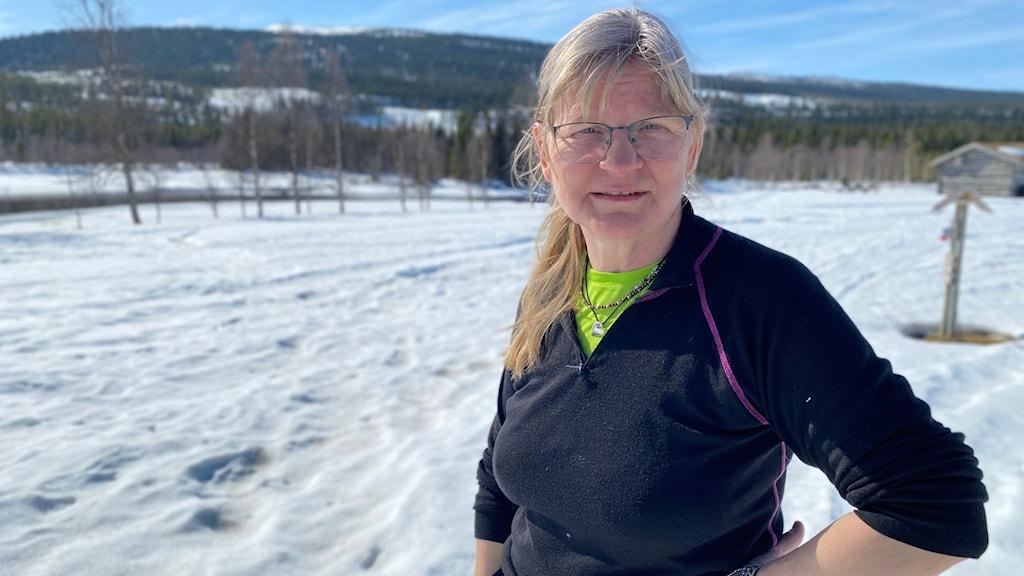 Ingrid Lind, driver Fiskecamping i Kraddsele, står på snö med berg i bakgrunden.