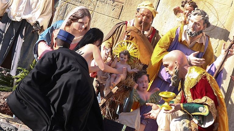 En vakt i Vatikanstaten försöker stoppa en Femen-aktivist från att stjäla jesusbarnet.