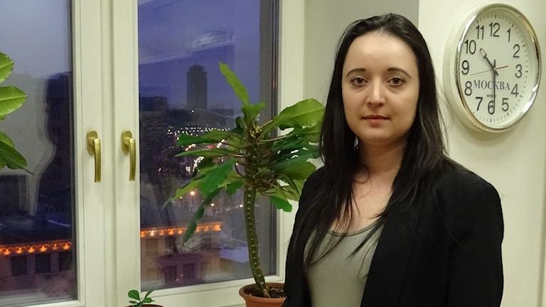 Kvinna med långt mörkt hår i rum med fönster