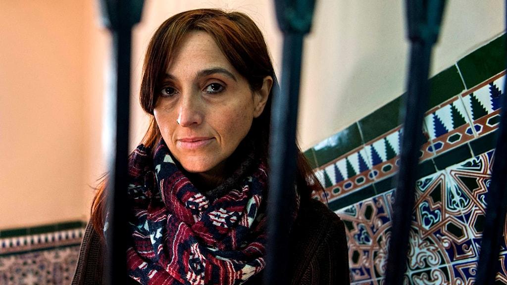 Kvinna med långt hår och halsduk sitter med ribbor i förgrunden