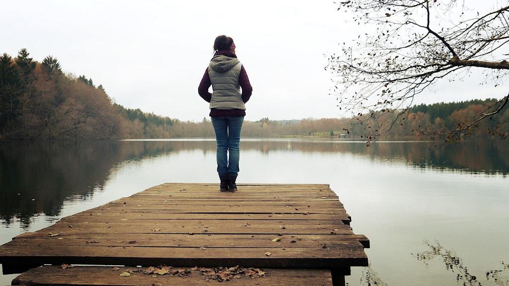 Kvinna står på en brygga vid vattnet