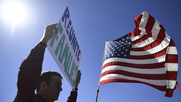 En amerikansk flagga och en man som håller upp en skylt med texten: Reunite families