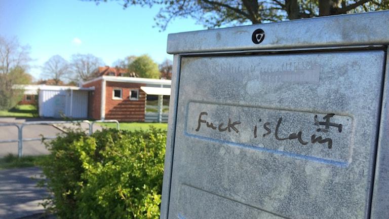 """Bilden visar klotter på ett elskåp i Skurup. Den engelska texten lyder """"Fuck islam"""". Bredvid har någon klottrat ett hakkors. Foto: Anna Bubenko/Sveriges Radio."""