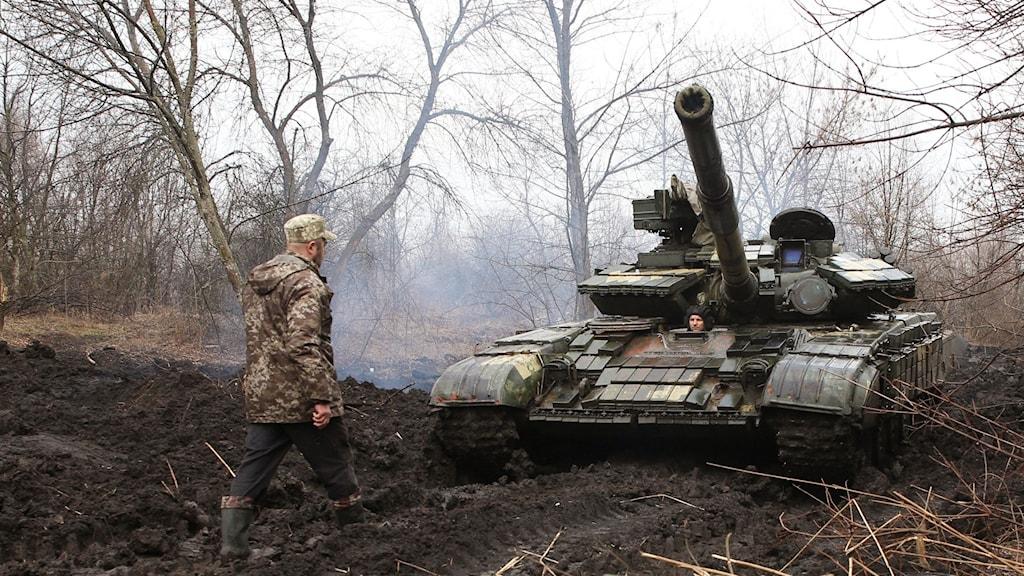 En ukrainsk soldat i skogen med en tank.