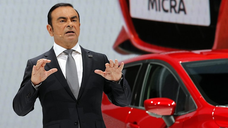 Carlos Ghosn framför en röd bil