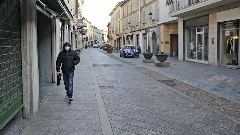 en man med skyddsmask på en annars tom gata i Codogno