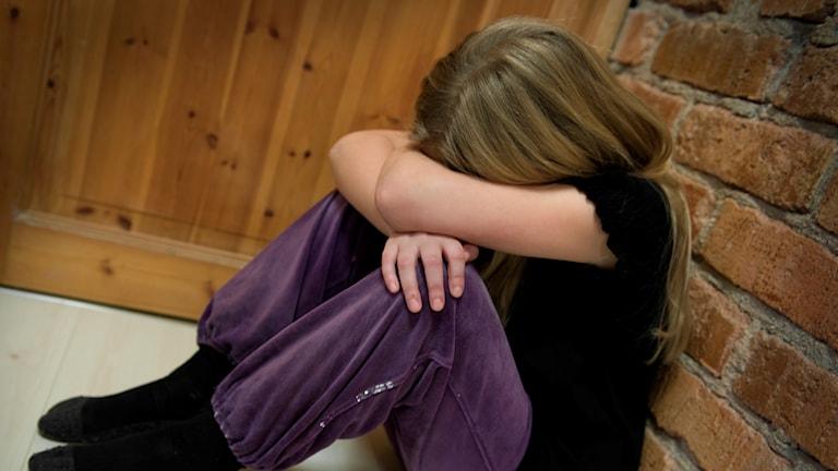 Ledsen flicka som sitter och gråter i ett hörn.