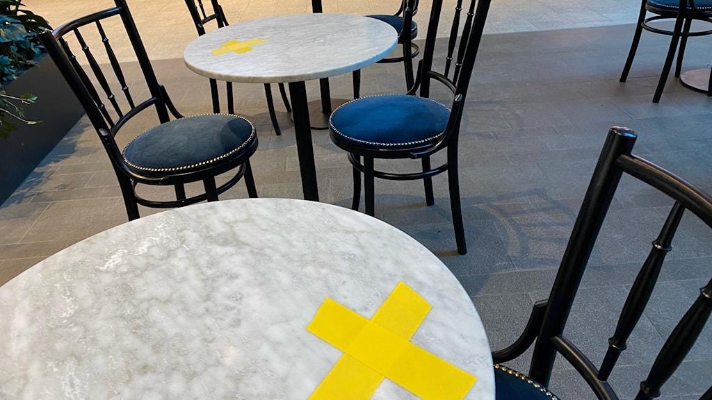 Serveringsbord med ett gult kryss tejpat på ena sidan.