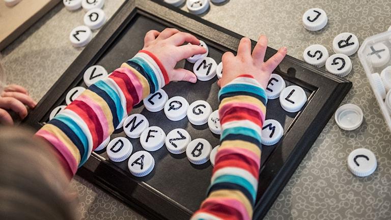 Ett barn på en förskola leker med bokstavsknappar.