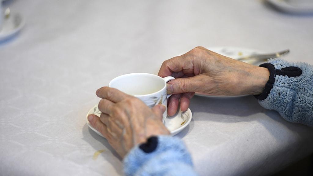 Äldre händer griper en kaffekopp vid ett bord.