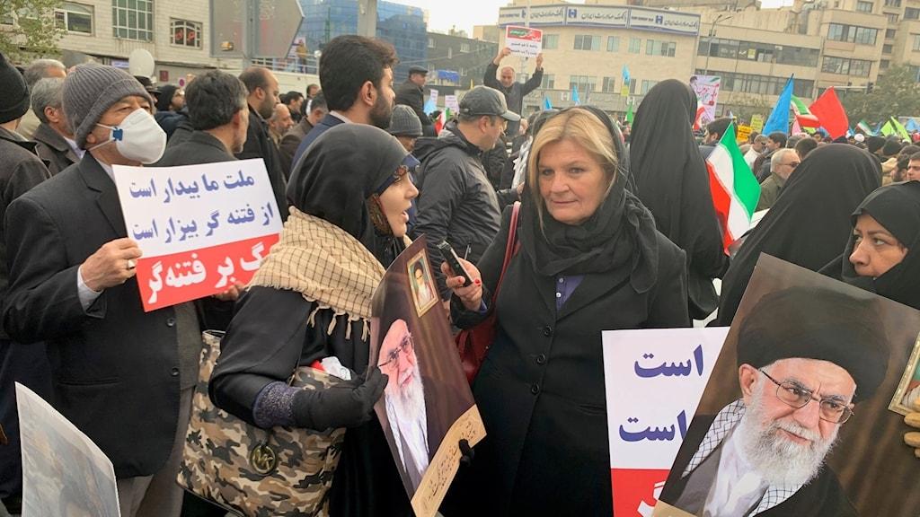 Cecilia Uddén intervjuar en av demonstranterna vid en manifestation för regimen.