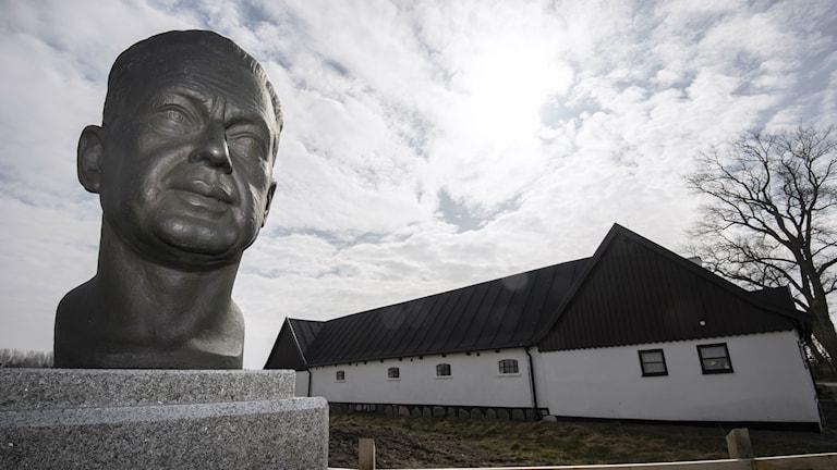 Bilden visar Dag Hammarskjölds gård Backåkra på Österlen i Skne, en vit, kringbyggd gård. I förgrunden skulptur av Dag Hammarskjöld. Foto: Johan Nilsson/TT.