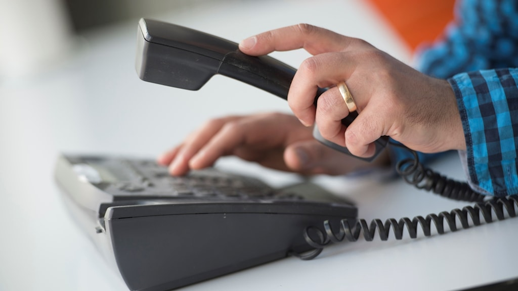 Man lyfter luren och slår ett nummer på telefonen.