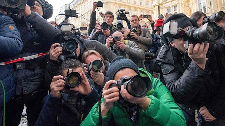 En stor massa journalister trängs för att fotografera Alexander Van der Bellen