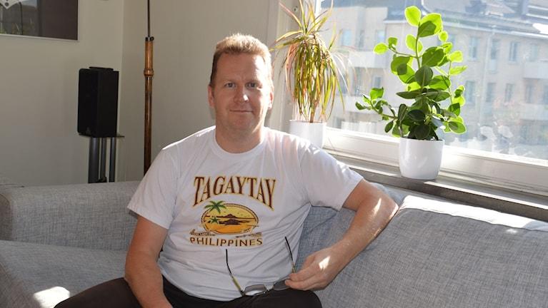 Man i vit t-shirt sitter i soff