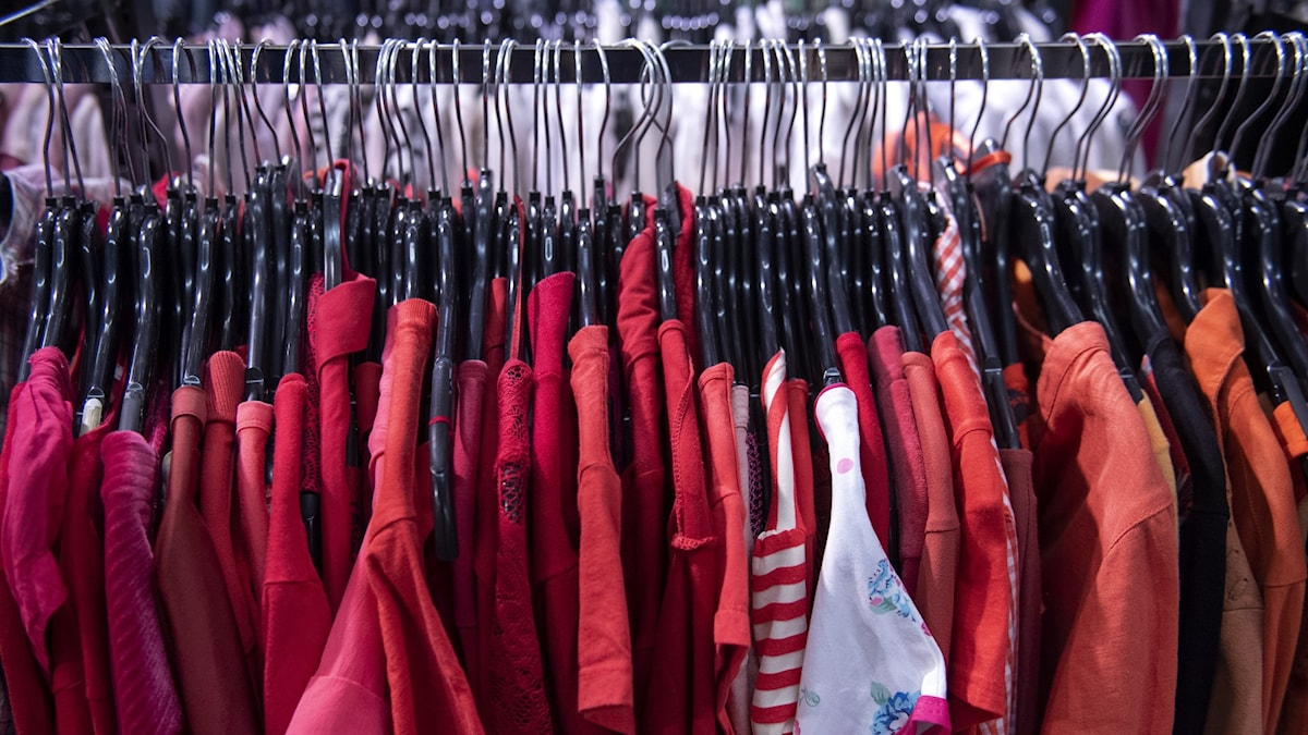 Kläder i röda toner som hänger på galgar på en klädställning.