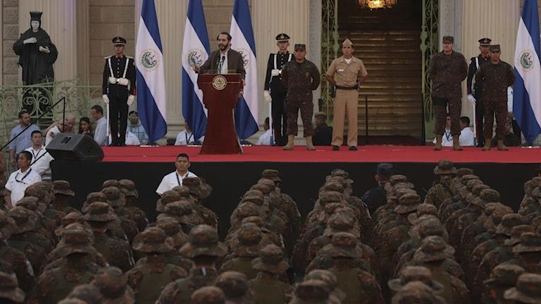 El Salvadors president Nayib Bukele talar framför soldater.