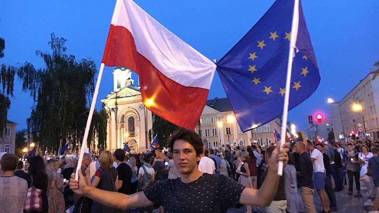 En ung man håller en polsk flagga och en EU-flagga.