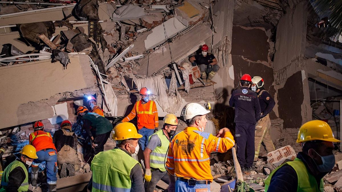 Personer är vid en byggnad som rasat samman.