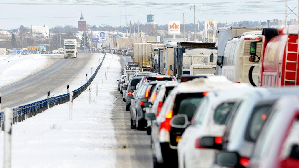 Lång kö av bilar ringlandes längs motorväg under vintern.