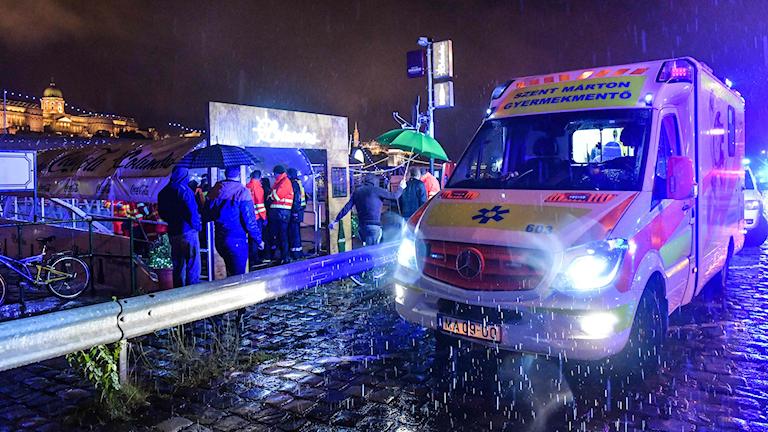 Ambulans vid flod, mörkt ute.