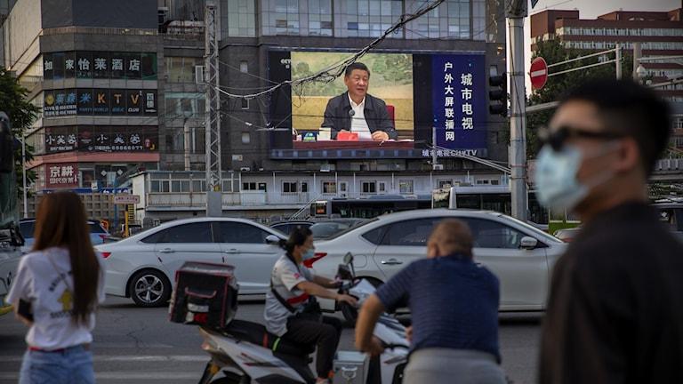Kinas president Xi Jinping visas på videoskärmar i Peking.