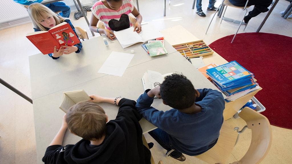 Fyra elever i årskurs fyra läser böcker.
