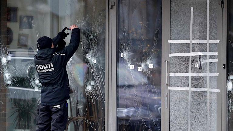 Polis undersöker kulhål i glas.