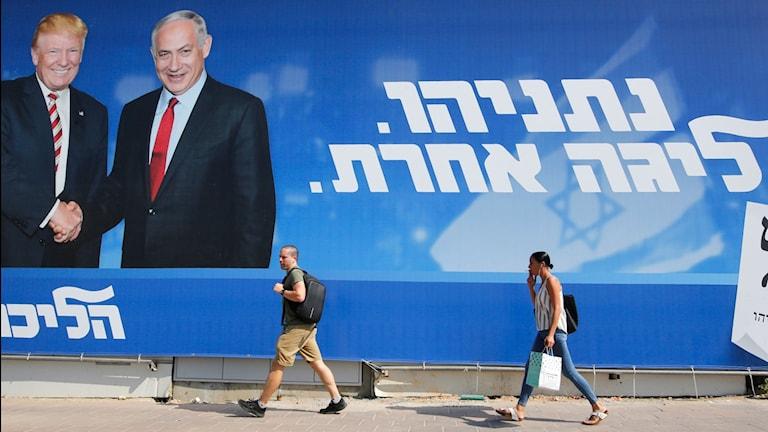 Väljare framför valaffisch för Netanyahus parti Likud. Foto: GIL COHEN-MAGEN/TT.