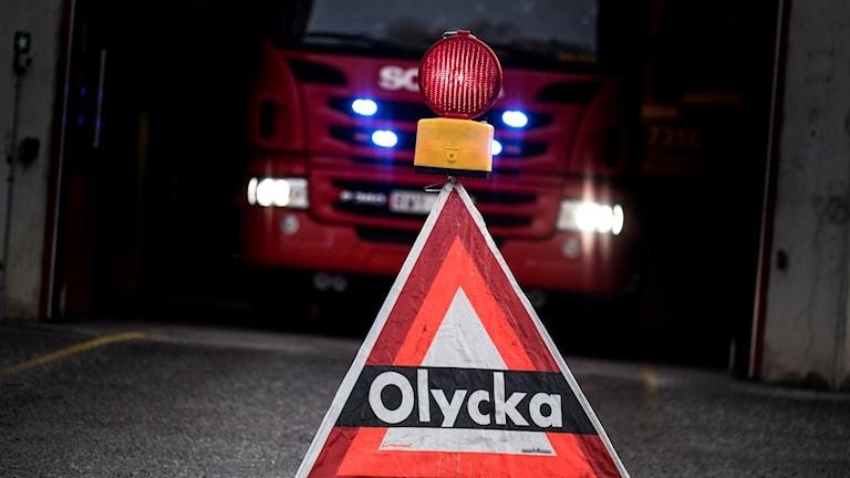 """En skylt med texten """"olycka"""" står framför en brandbil."""