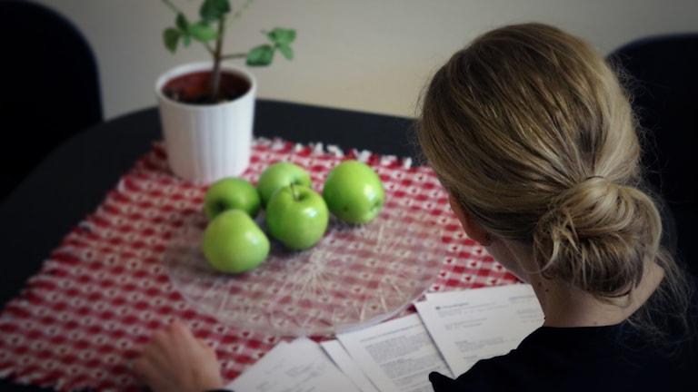 Bilden visar en kvinna som sitter vid ett bord, med papper från Kronofogden framför sig. Foto: Liv Widell/Sveriges Radio.