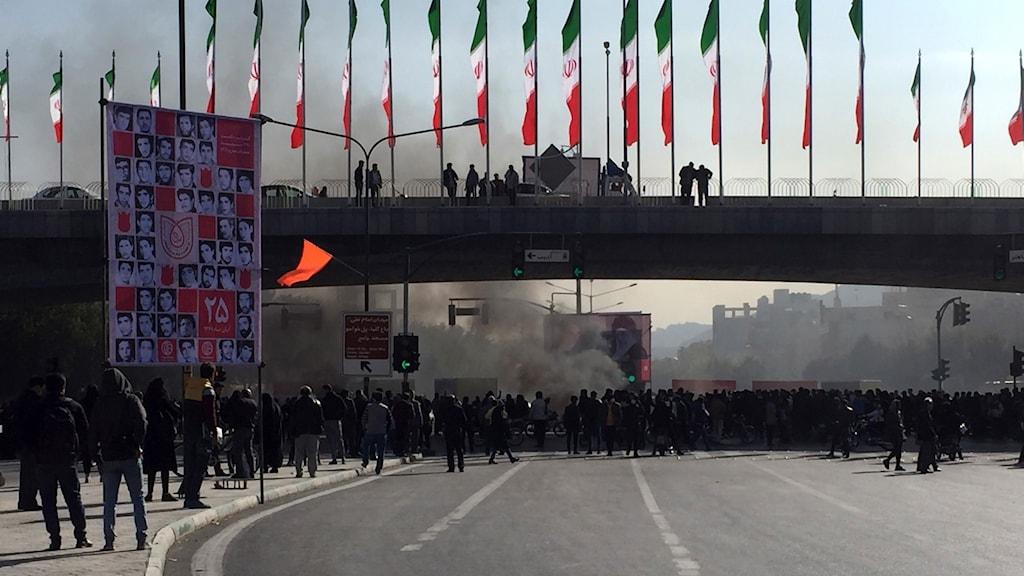 Människor demonstrerar på motorväg. Iranska flaggor.
