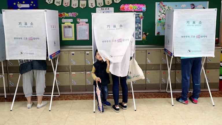 En pojke väntar medans mamman röstar i en röststation Sydkoreas huvudstad Seoul.