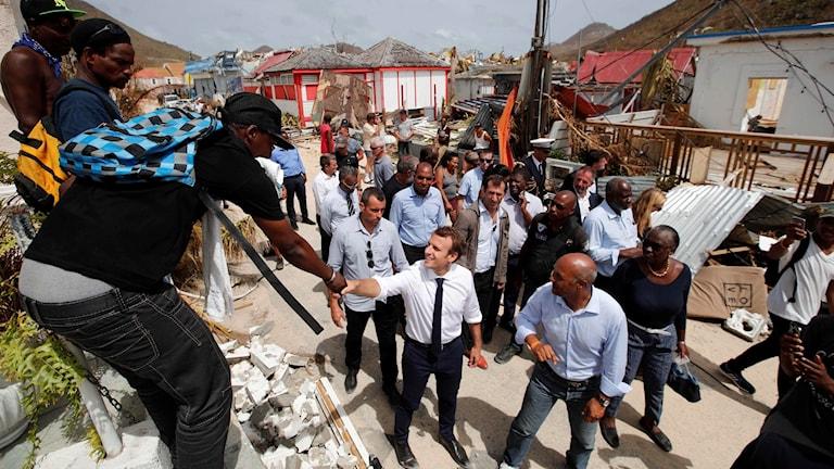 En man skakar hand med en annan man. Runt dem står flera andra män.