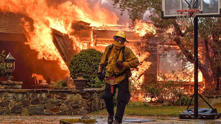 Brandman går utanför ett övertänt hus i Anaheim Hills, Kalifornien.