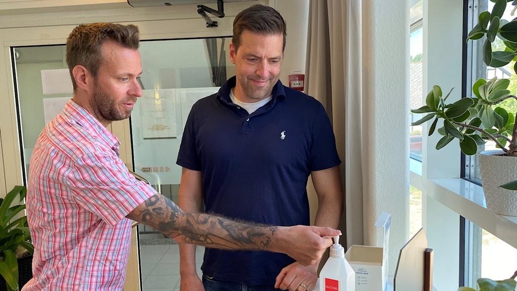 Två män står vid en handspritpump