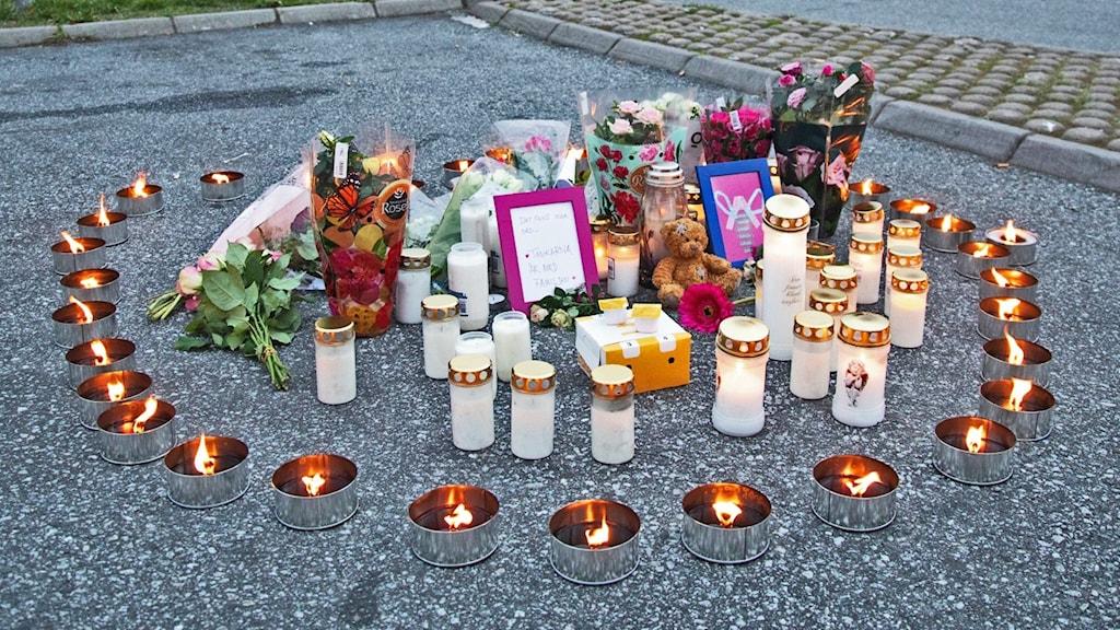 Ljus och blommor på en parkeringsplats, minnesplats efter att en 12-årig flicka blev skjuten här.