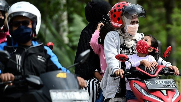 En mamma med sitt barn på en motorcykel.