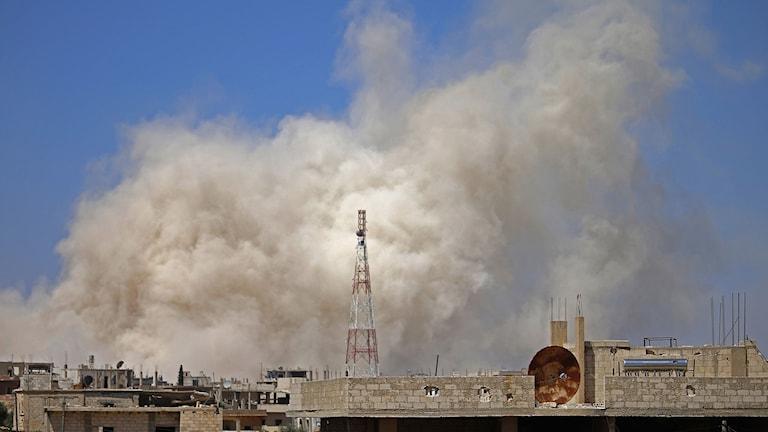 Rök stiger upp mot himlen i Daraa efter syriska bombningar.