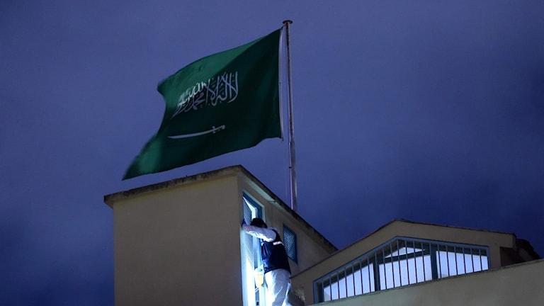 Saudisk flagga med en turkisk polis bredvid.