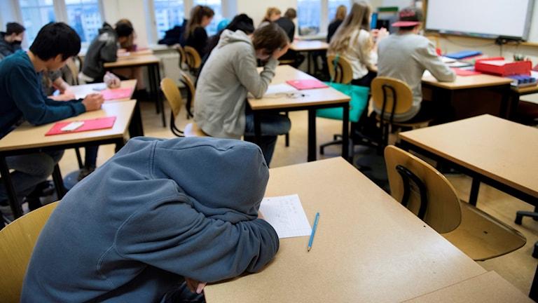 En trött högstadieelev i årskurs 8 sover med huvudet på bänken under en lektionEn trött högstadieelev i årskurs 8 sover med huvudet på bänken under en lektion.