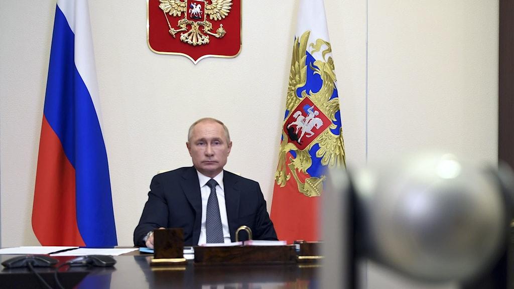 Allvarlig man klädd i mörk kostym och slips sitter vid stort bord ned två flaggor och en sköld bakom sig