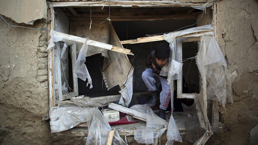 En pojke inspekterar sitt förstörda hem efter en attack i Kabul, Afghanistan.
