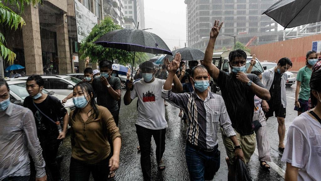 Folk går på gata i Myanmar i regn.